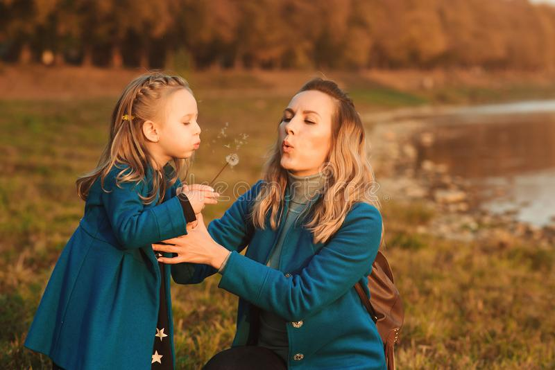 Mother with small daughter blowing to dandelion in nature outdoors. Happy family, childhood and lifestyle concept. Happy loving royalty free stock photo