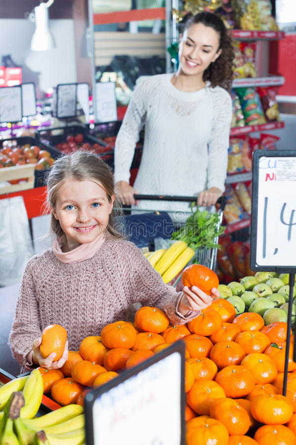 Mother and small pretty daughter buying citrus fruits. Cheerful positive mother and small pretty daughter buying sweet citrus fruits royalty free stock photography