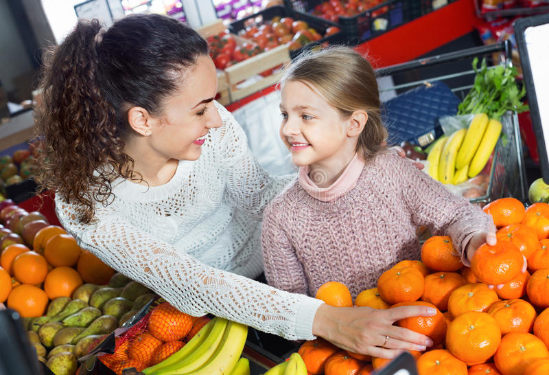 Mother and small pretty daughter buying citrus fruits. Positive mother and small pretty daughter buying sweet citrus fruits royalty free stock image