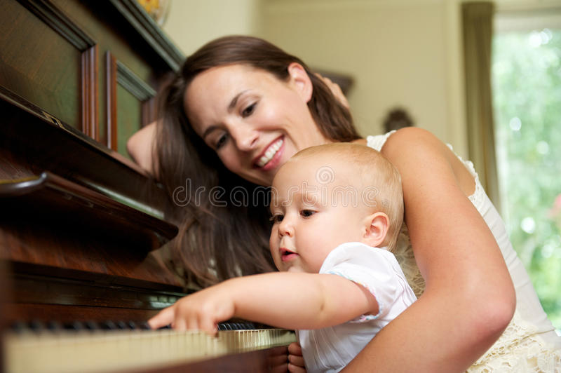 Download Mother Smiling As Baby Plays Piano Royalty Free Stock Photography - Image: 32571557