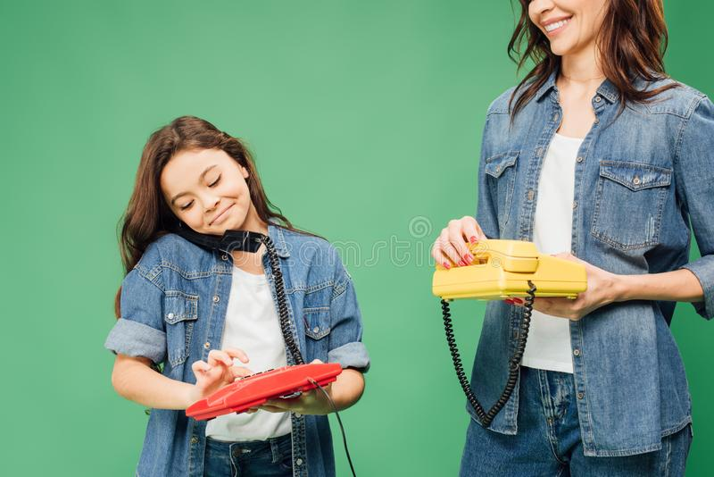 Mother and smiling daughter holding vintage telephones isolated. On green stock photography