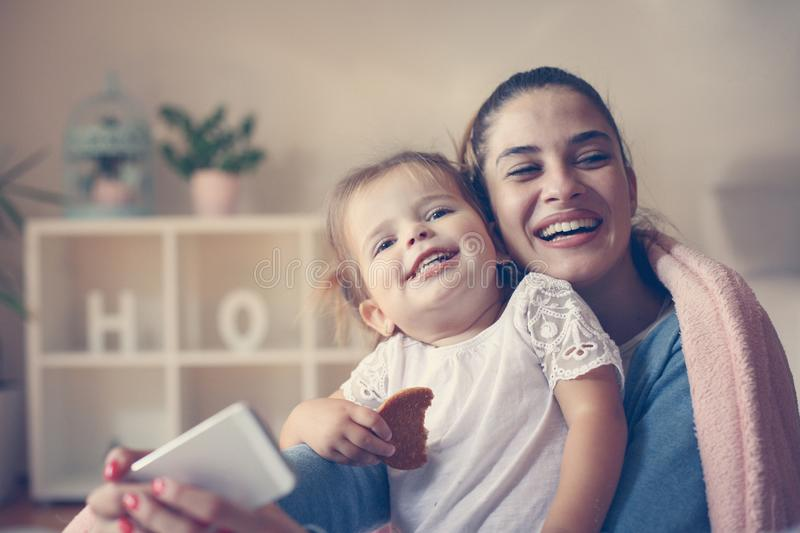 Mother and smiling girl taking self picture at home. Cheerful mother and smiling girl taking self picture at home royalty free stock image