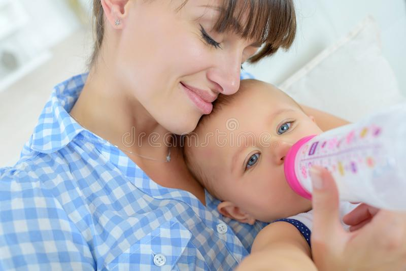 Mother snuggling baby during feed royalty free stock photo
