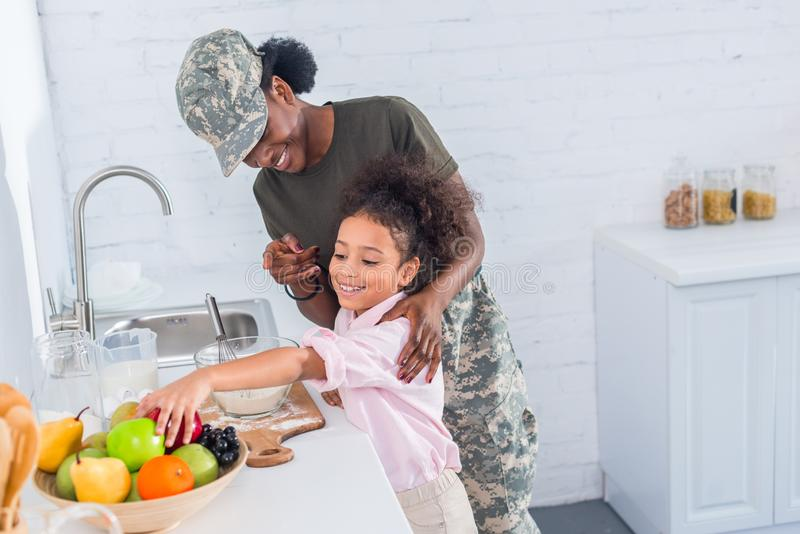 Mother soldier and african american child. Cooking together royalty free stock images