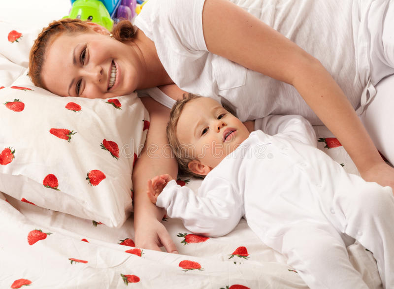 Mother and son. Are lying on the bed and looking at camera. Focus is on baby's face royalty free stock images