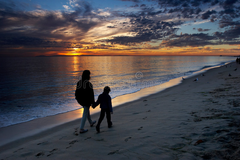 Mother and son. Walking on the beach and watching colorful sunset