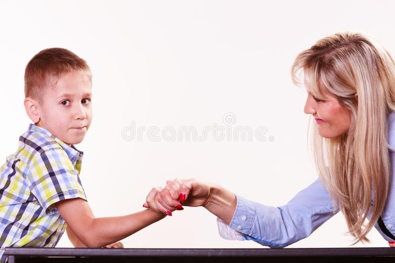 Mother and son arm wrestle sit at table. Spending time with family fun and family bonds. Mother and son arm wrestle and have fun indoors royalty free stock photos