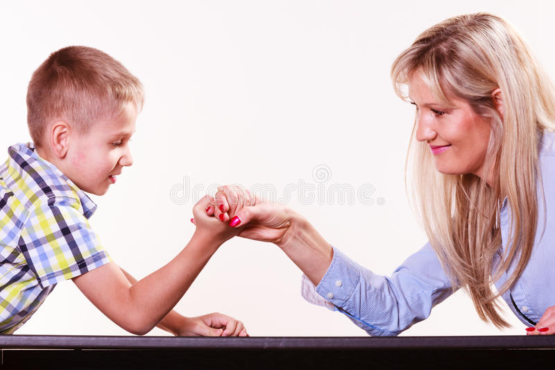 Mother and son arm wrestle sit at table. Spending time with family fun and family bonds. Mother and son arm wrestle and have fun indoors stock photo