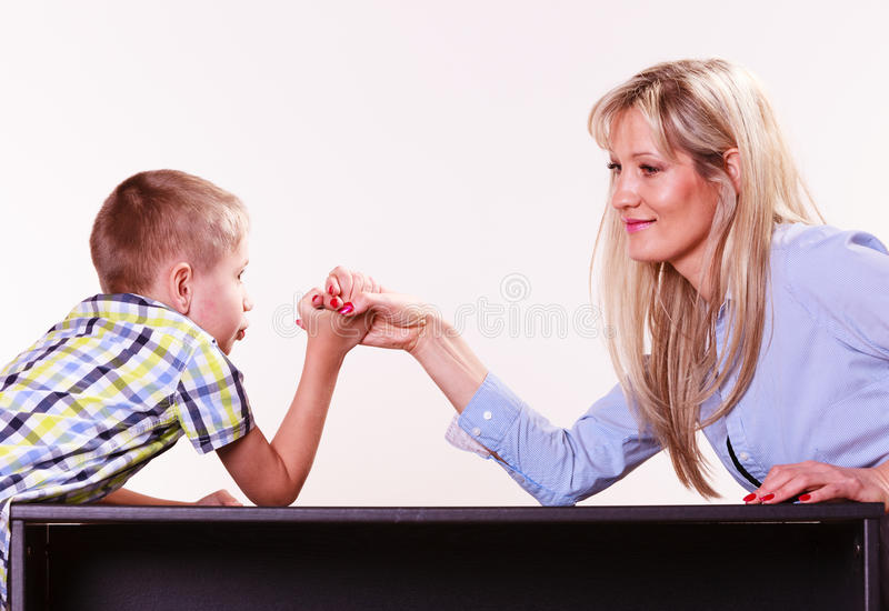 Mother and son arm wrestle sit at table. Spending time with family fun and family bonds. Mother and son arm wrestle and have fun indoors stock photos
