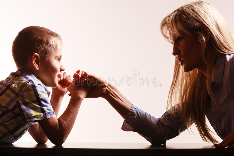 Mother and son arm wrestle sit at table. Spending time with family fun and family bonds. Mother and son arm wrestle and have fun indoors royalty free stock photography