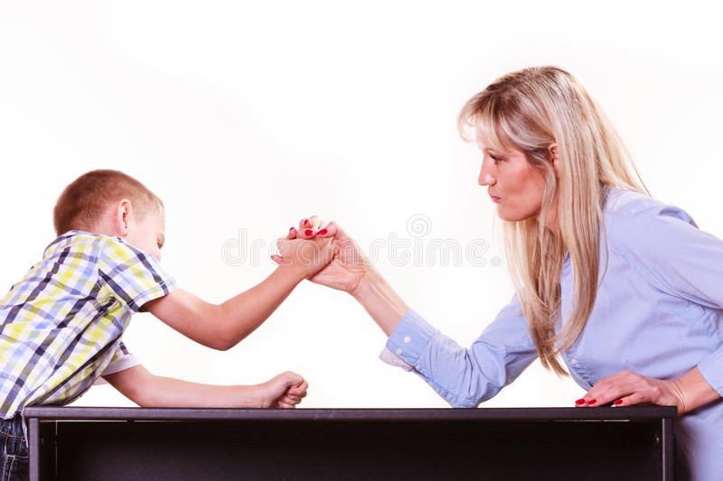 Mother and son arm wrestle sit at table. Spending time with family fun and family bonds. Mother and son arm wrestle and have fun indoors stock images