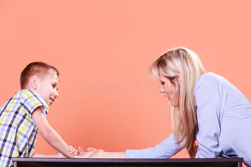 Mother and son arm wrestle sit at table. Spending time with family fun and family bonds. Mother and son arm wrestle and have fun indoors royalty free stock images