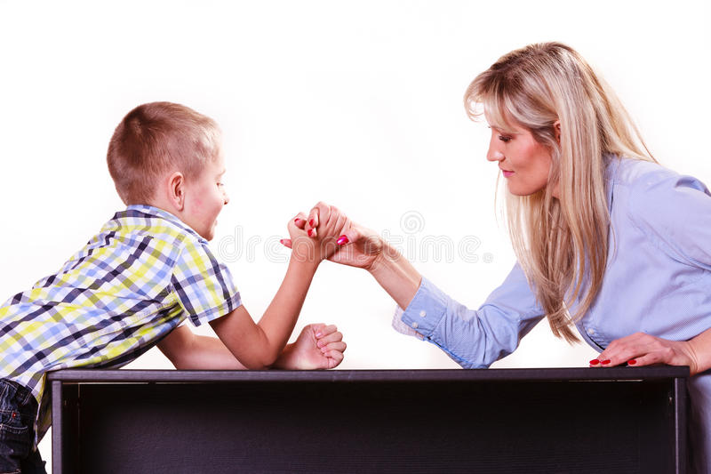 Mother and son arm wrestle sit at table. Spending time with family fun and family bonds. Mother and son arm wrestle and have fun indoors stock photography
