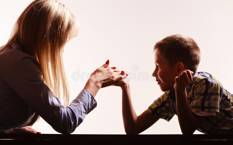 Mother and son arm wrestle sit at table. Spending time with family fun and family bonds. Mother and son arm wrestle and have fun indoors stock image