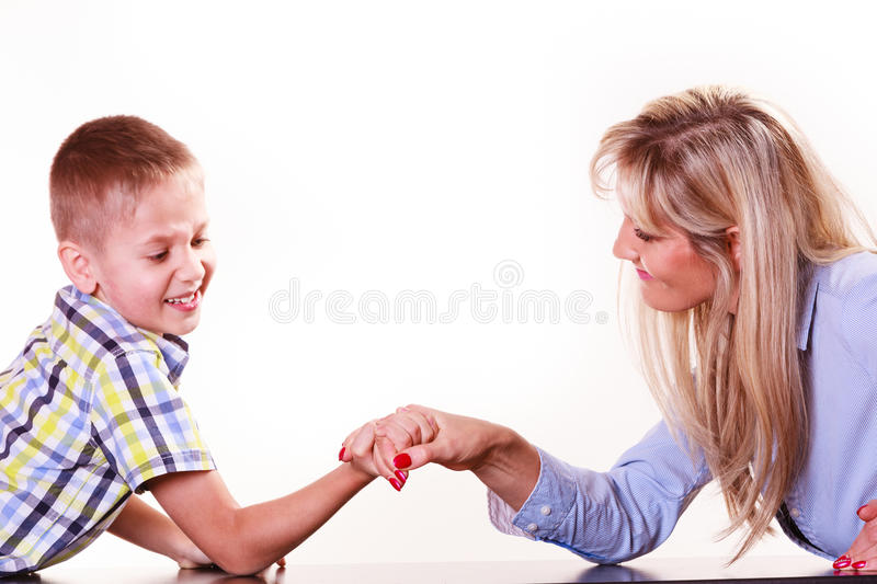 Mother and son arm wrestle sit at table. Spending time with family fun and family bonds. Mother and son arm wrestle and have fun indoors royalty free stock photo
