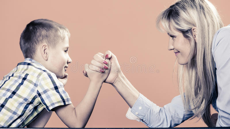 Mother and son arm wrestling. Family, children and motherhood concept. Son confronts his middle aged mother. Woman and little boy arm wrestling having fun stock photos