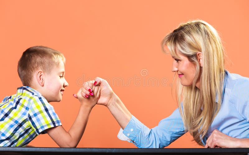 Mother and son arm wrestling. Family, children and motherhood concept. Son confronts his middle aged mother. Woman and little boy arm wrestling having fun stock photo