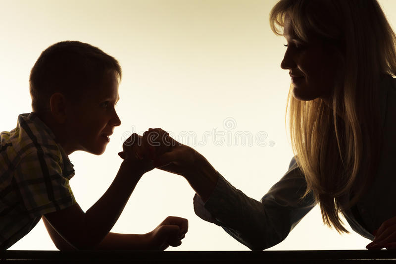 Mother and son arm wrestling. Family, children and motherhood concept. Silhouette son confronts his middle aged mother. Woman and little boy arm wrestling stock photography
