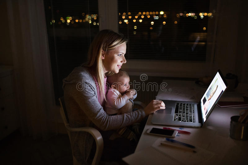 Mother with son in the arms, working on laptop royalty free stock images