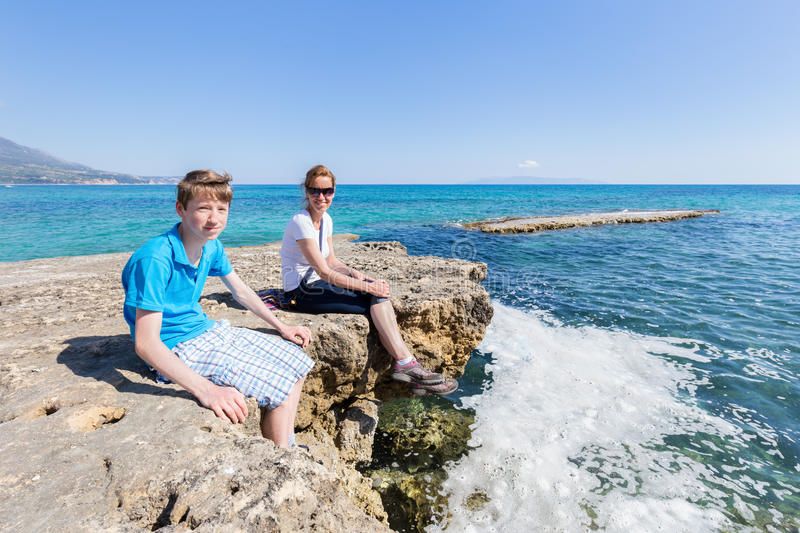 Mother and son as tourists sitting on rock near sea stock photo