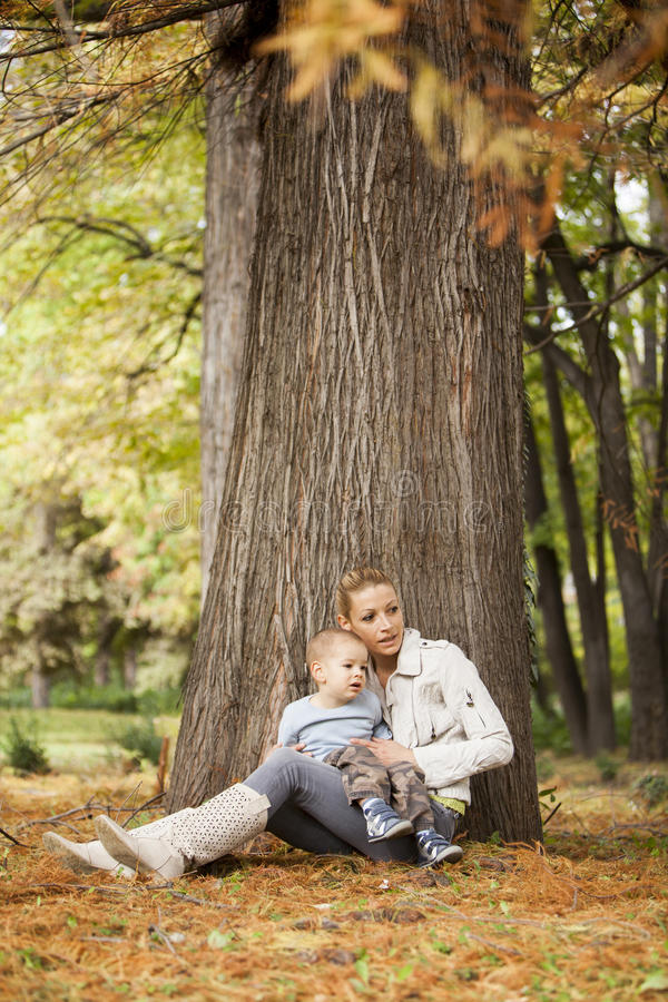 Mother and son in the autumn forest stock photo