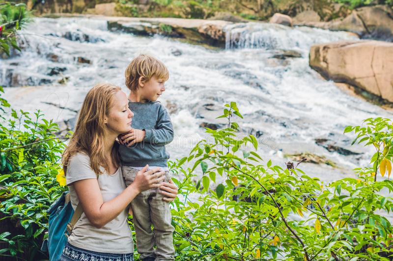 Mother and son on the background of Beautiful Camly waterfall In Da Lat city.  royalty free stock photos