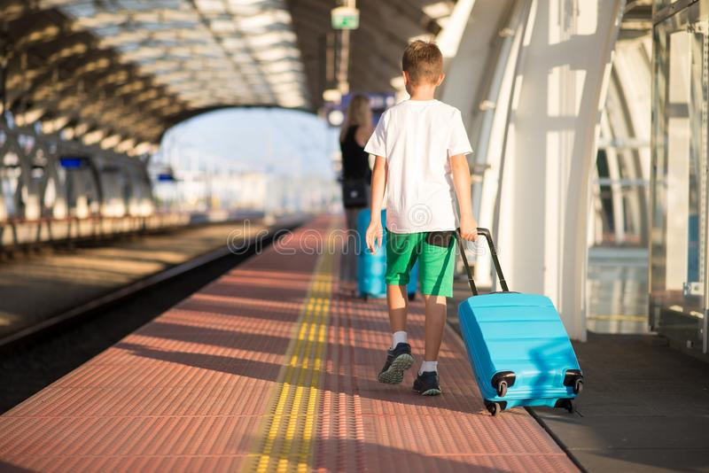 Mother and son with blue baggage suitcase walking on train station platform royalty free stock image