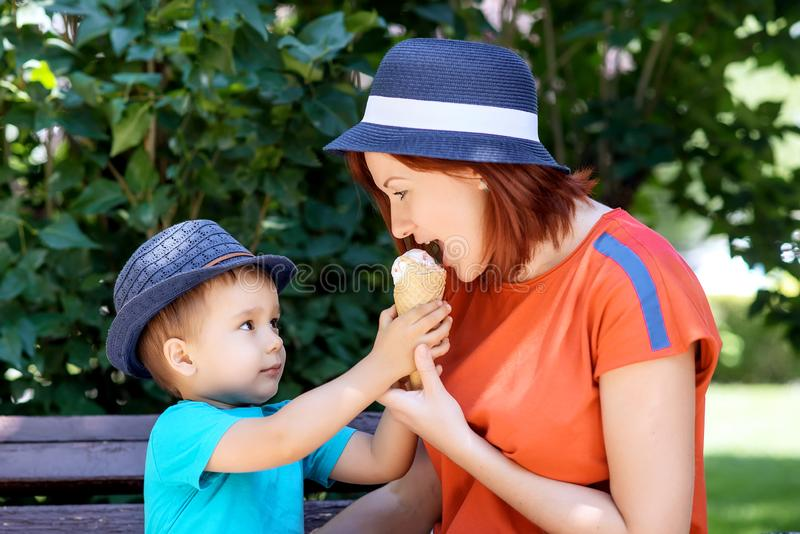 Mother and son in blue hats together sit on bench, boy is sharing with mom ice-cream in waffle cone royalty free stock images