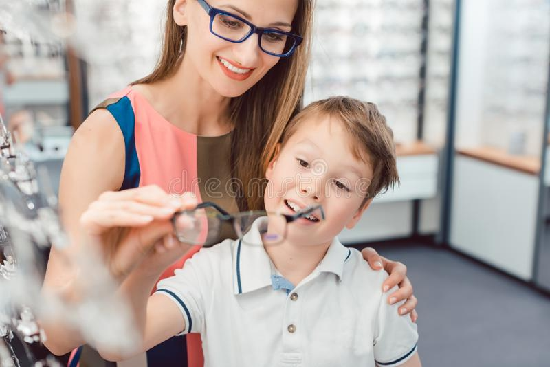 Mother and son both liking the eyeglasses offered in optician shop. Being excited stock images