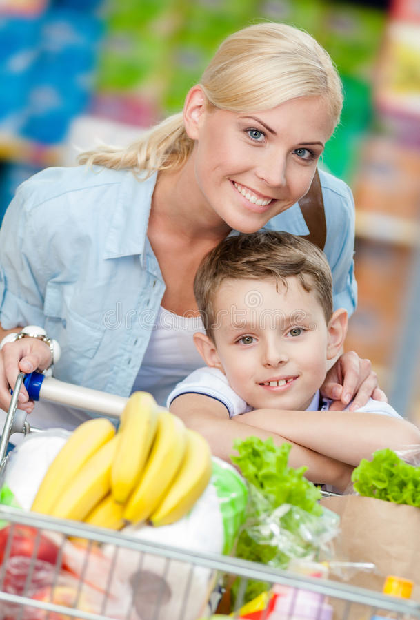 Mother and son with cart full of products in shop. Concept of healthy food and consumerism royalty free stock photography