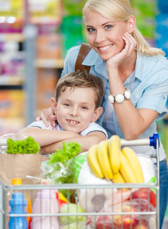 Mother and son with cart full of products in shopping center. Mother and son with cart full of products in shopping mall. Concept of healthy food and consumerism stock photography