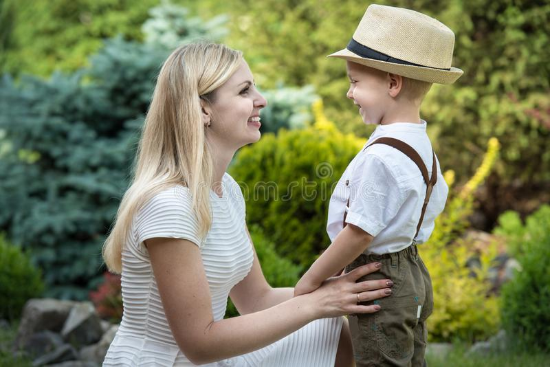 Life moment of happy family! Mother and son child playing having fun together on the grass in sunny summer day stock photography
