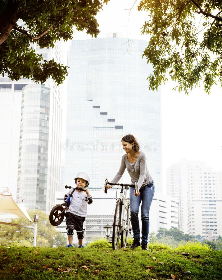 Other and son cycling in the park stock image