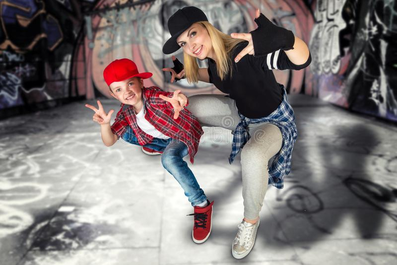 Mother and son dance hip-hop.Urban lifestyle. Hip-hop generation.Graffiti on the walls. stock images