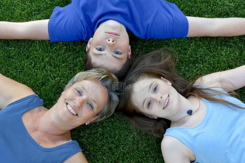 Mother son and daughter lying in the meadow. Mother and her two teenage kids lying in the meadow, all dressed in blue stock photos