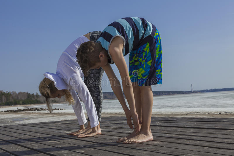 mother and son doing stretching exercises on the beach stock photo