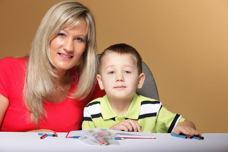 Mother and son drawing together. Mom helping with homework daycare brown background royalty free stock photo