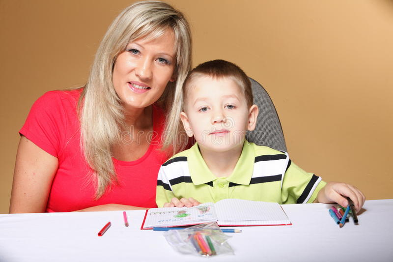 Mother and son drawing together. Mom helping with homework daycare brown background stock image
