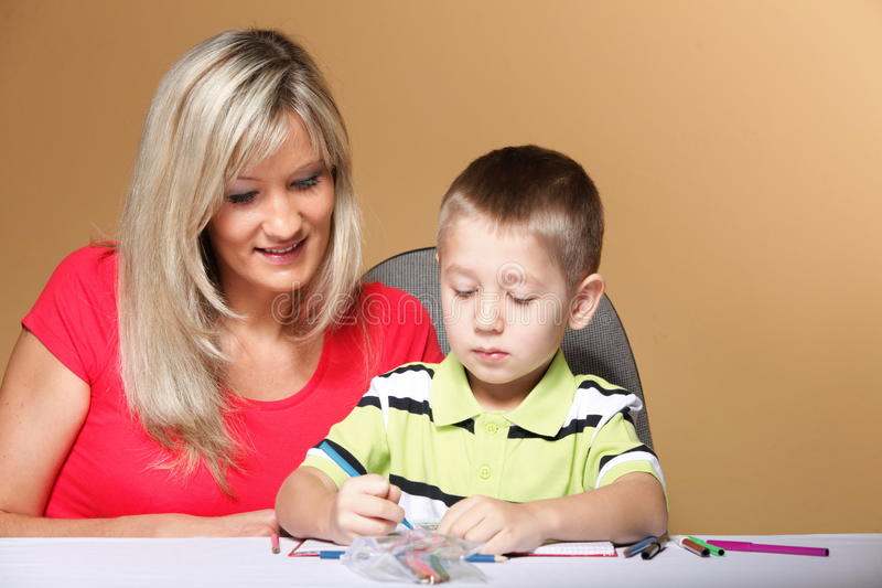 Mother and son drawing together. Mom helping with homework daycare brown background stock images