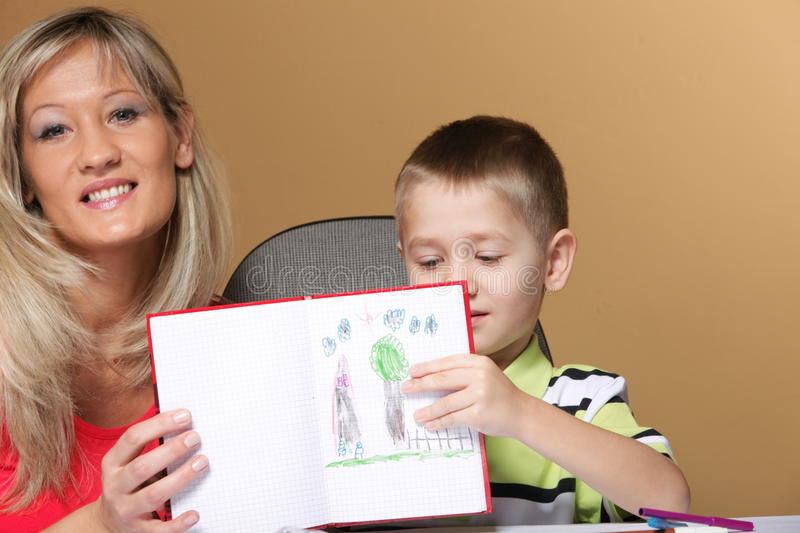 Mother and son drawing together. Mom helping with homework daycare brown background stock photography