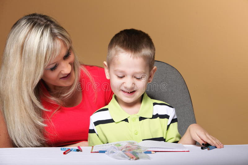 Mother and son drawing together. Mom helping with homework daycare brown background royalty free stock image