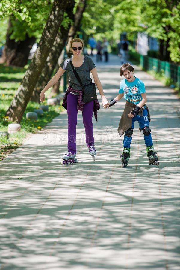 Mother and son driving inline skates stock photo