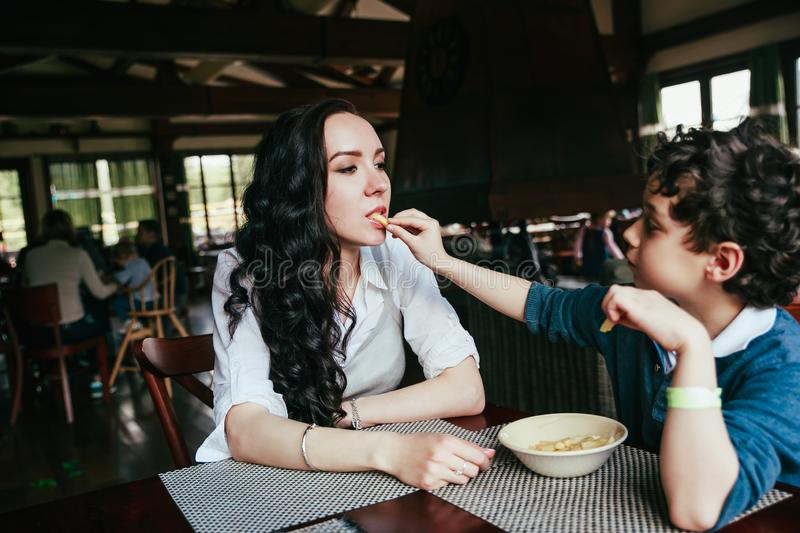 Mother and son eating fries in restaurant. Funny family dinner stock image