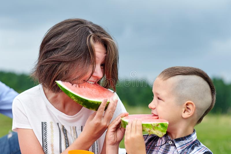 Mother and son eating watermelon in meadow or park. Happy family on picnic. outdoor portrait royalty free stock photography