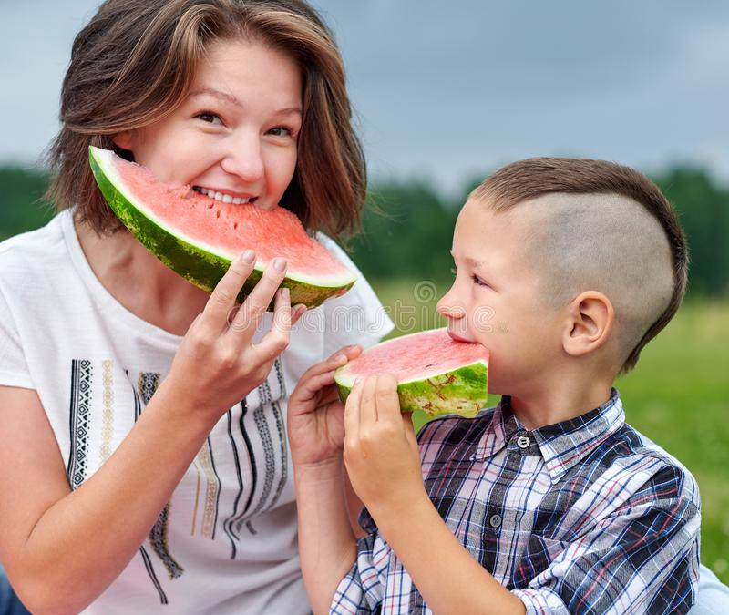 Mother and son eating watermelon in meadow or park. Happy family on picnic. outdoor portrait stock photo