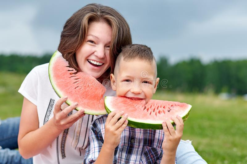 Mother and son eating watermelon in meadow or park. Happy family on picnic. outdoor portrait royalty free stock photos