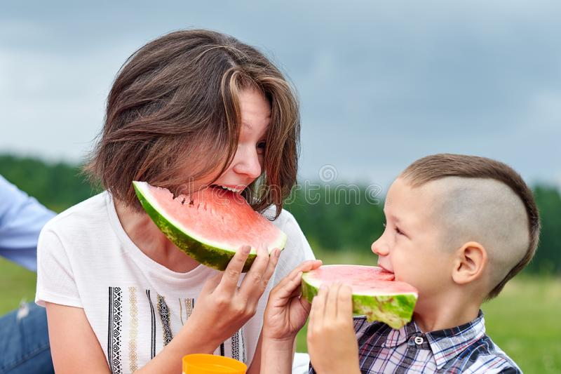 Mother and son eating watermelon in meadow or park. Happy family on picnic. outdoor portrait Little boy and mom royalty free stock photography