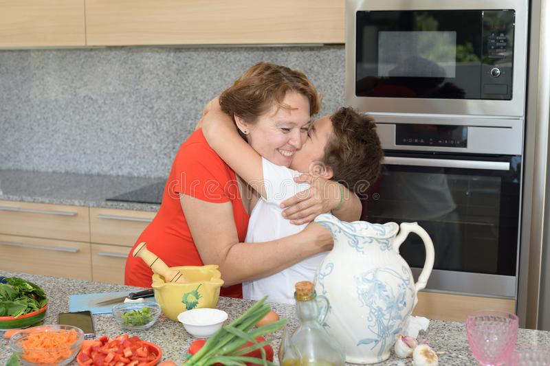 Mother and son embrace while preparing lunch stock images