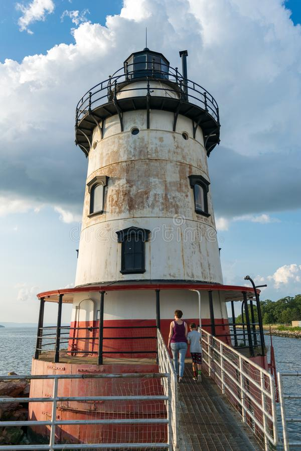 A mother and son entering the Sleepy Hollow Lighthouse, on a beautiful summer`s day, against a blue sky with beautiful royalty free stock photography