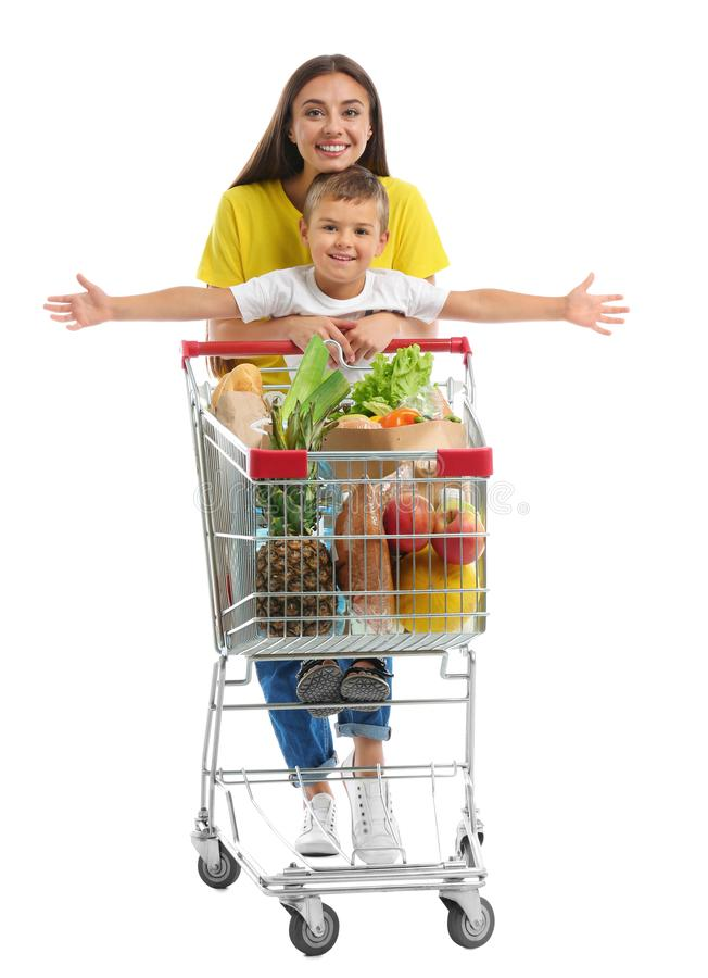 Mother and son with full shopping cart on background royalty free stock photography